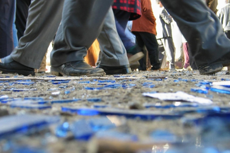 <p>Iraqis walk on broken window glass after an explosion at the Kurdish Democratic Party headquarters in Baquba, 60kms northeast of Baghdad, in January 2005. Today, Iraq is as fractured as ever.</p>