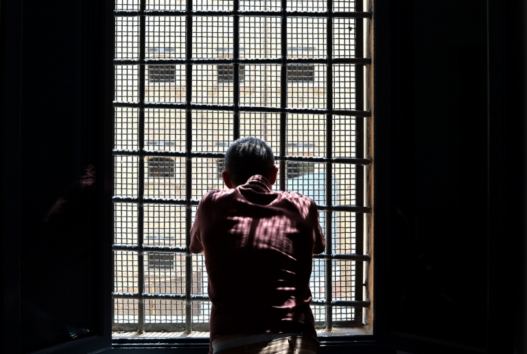 <p>A prisoner looks out a window at Regina Coeli prison in Rome on May 30, 2014.</p>