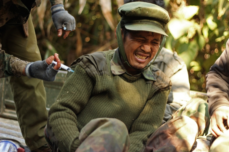 <p>An injured rebel Kachin Independence Army (KIA) 3rd Brigade soldier gets an injection from a medic on Hka Ya mountain in Kachin province on January 20, 2013.</p>