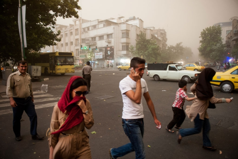 <p>Iranians walk amidst dust as a sandstorm engulfs the capital Tehran on June 2, 2014.</p>