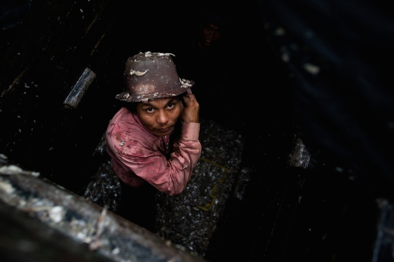 <p>A laborer from Myanmar works in the hull of a Thai fishing vessel. Trash fish caught by forced laborers is a key ingredient in fish sauce, pet food and shrimp feed.</p>