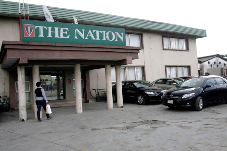 <p>A woman walks to the corporate headquarters of The Nation newspaper in Lagos, Nigeria on Oct. 13, 2011.</p>