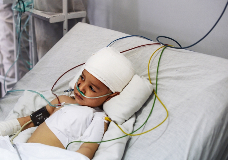 <p>Abuzar Ahmad, the only surviving child of Afghan journalist Sardar Ahmad, who was killed with his wife and two other children in an attack at a Kabul hotel, lies in bed in the intensive care unit of a local hospital on March 24, 2014.</p>