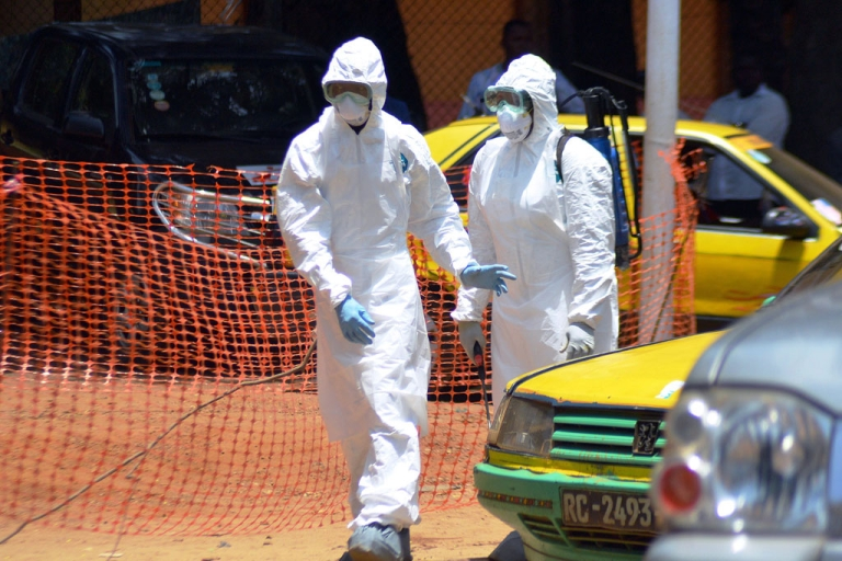 <p>Two members of the Guinean Red Cross, in protective gear, arrive on March 31, 2014 to evacuate the bodies of two people who died from the Ebola virus in an isolation ward at the Donka hospital in Conakry, Guinea.</p>