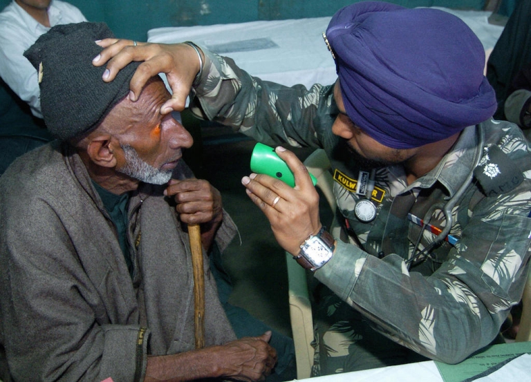<p>An Indian army doctor (R) checks the eyes of a Kashmiri man during a medical camp in Mujpather, some 45 Kms from Srinagar, 31 March 2007.  Many medical practitioners in India are not properly trained.</p>