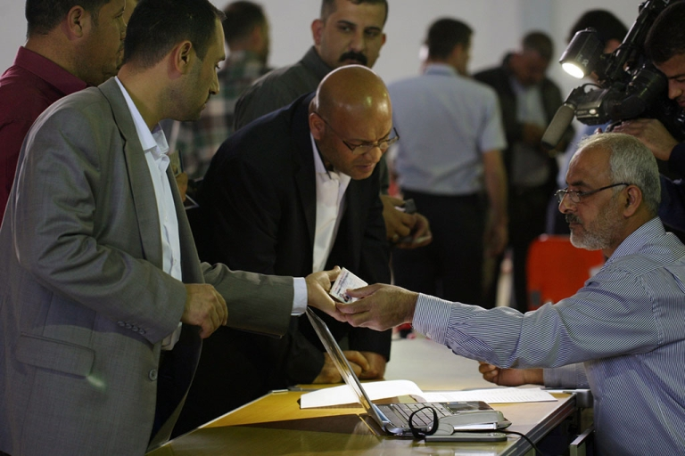 <p>An Iraqi election commission official hands over electronic voter ID cards to Iraqi policemen in the central city of Najaf on March 2, 2014, ahead of legislative elections in April.</p>