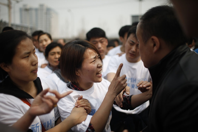 <p>A relative (C) of passengers on missing Malaysia Airlines flight MH370 yells at a security personnel (R) while she attends a protest outside the Malaysian embassy in Beijing on March 25, 2014.</p>