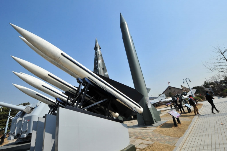 <p>Visitors walk past replicas of a North Korean Scud-B missile (R) and South Korean Hawk surface-to-air missiles (L) at the Korean War Memorial in Seoul on March 3, 2014.</p>