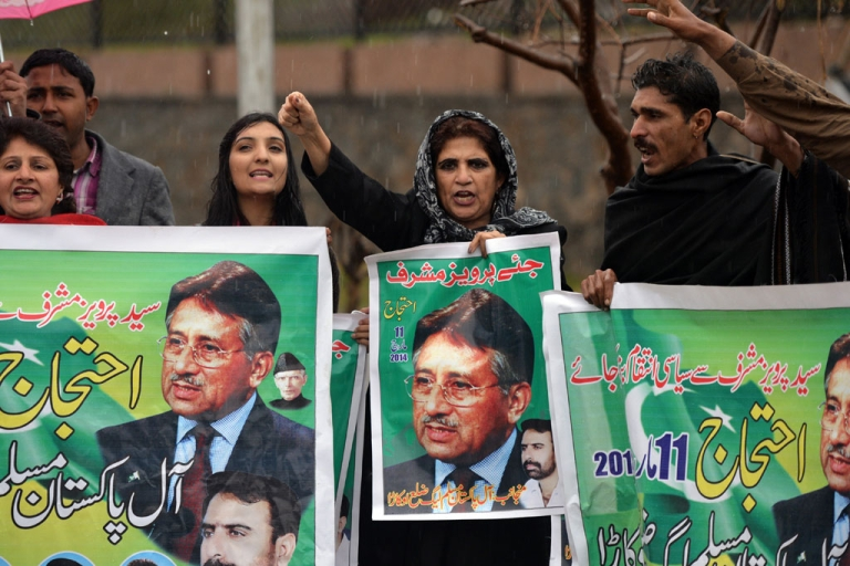 <p>Pakistani supporter of former military ruler Pervez Musharraf shout slogans as they hold banners with images of Musharraf outside a special court set up to try Musharraf during a hearing in Islamabad on March 11, 2014.</p>