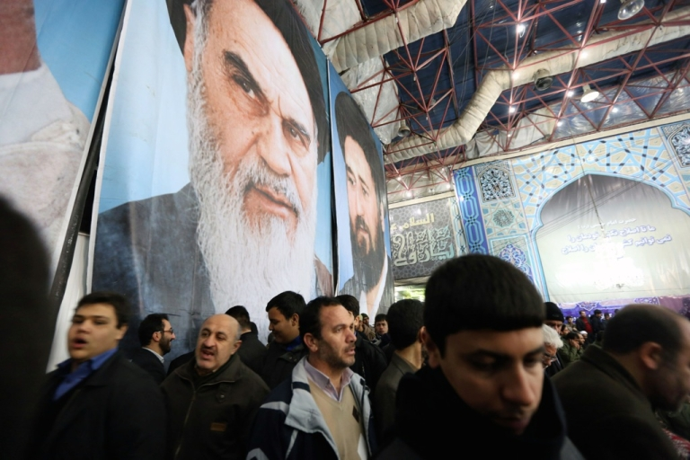 <p>Iranian men gather in front of a giant portrait of the founder of Iran's Islamic Republic, Ayatollah Ruhollah Khomeini on February 1, 2014 at Khomeini's mausoleum in a suburb of Tehran during the festivities marking the 35th anniversary of his return from exile. Khomeini returned from exile in 1979, the trigger for a revolution which spawned an Islamic state now engulfed in a deep political crisis. AFP PHOTO/ATTA KENARE        (Photo credit should read ATTA KENARE/AFP/Getty Images)</p>