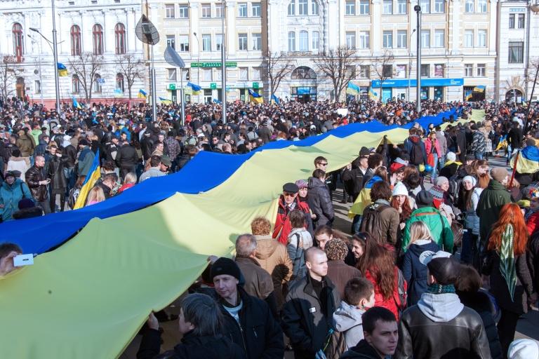 <p>Demostrators carry a giant Ukrainian flag during an anti-war rally in northeastern Kharkiv.</p>