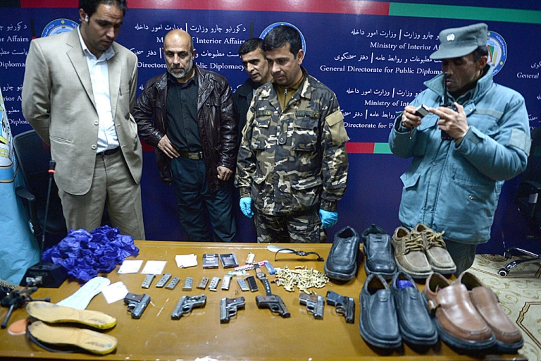 <p>Afghan security officials display weapons and items used by gunmen who attacked the Serena hotel in Kabul on March 20, 2014. At least nine civilians including an Agence France-Presse reporter, two of his children and four foreigners were killed in a Taliban attack on the luxury hotel in Kabul, officials said a day later.</p>