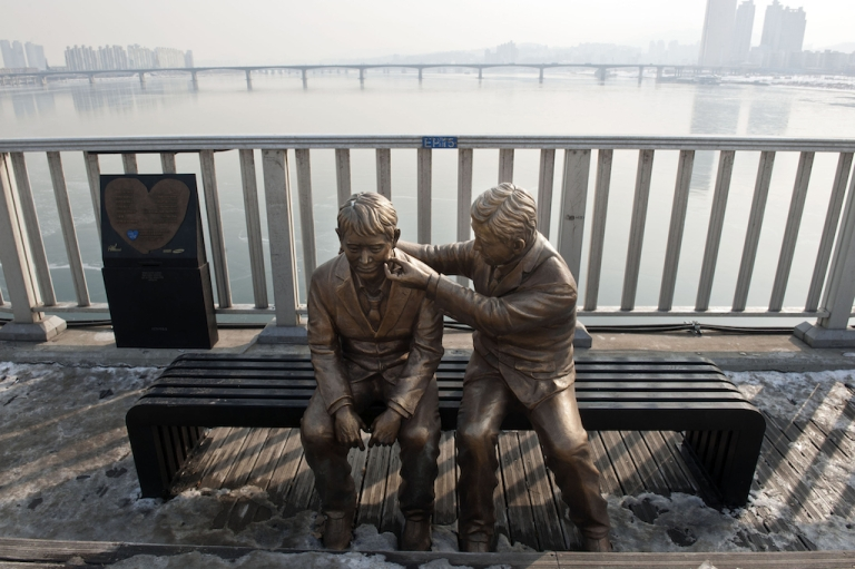 <p>South Korea's government installed this statue of a man comforting another person, in an attempt to address the many suicides at the Mapo Bridge. Two recent high profile suicides have shocked the nation.</p>