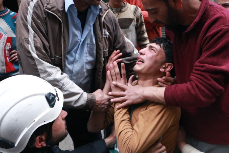 <p>A man is comforted by a rescue worker and others following a reported air strike by government forces in which a fellow rescue worker was killed on March 9, 2014 in the northern city of Aleppo.</p>