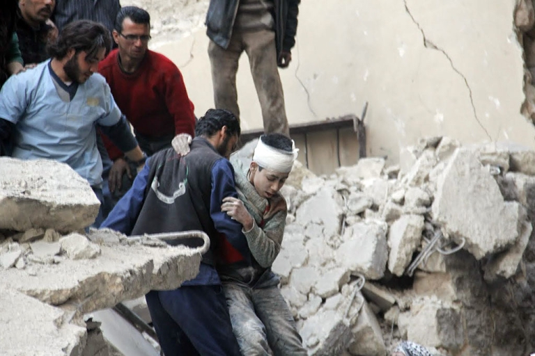 <p>Syrian men rescue a wounded boy from the rubble of a destroyed building following a reported air strike by Syrian government forces on the Kallassa neighborhood in the northern city of Aleppo on Feb. 26, 2014.</p>