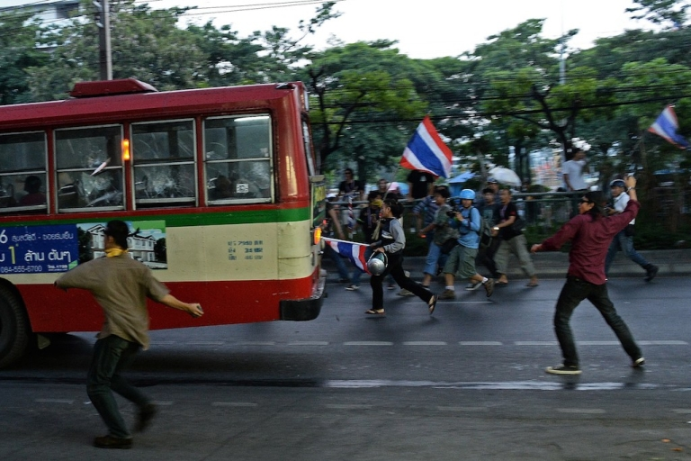 <p>Thai opposition protesters throw rocks at a bus carrying pro-government Red Shirt supporters on their way to a rally at a stadium in Bangkok on November 30, 2013. The Red Shirts are preparing for armed resistance in the event that their government is overthrown by yet another coup.</p>