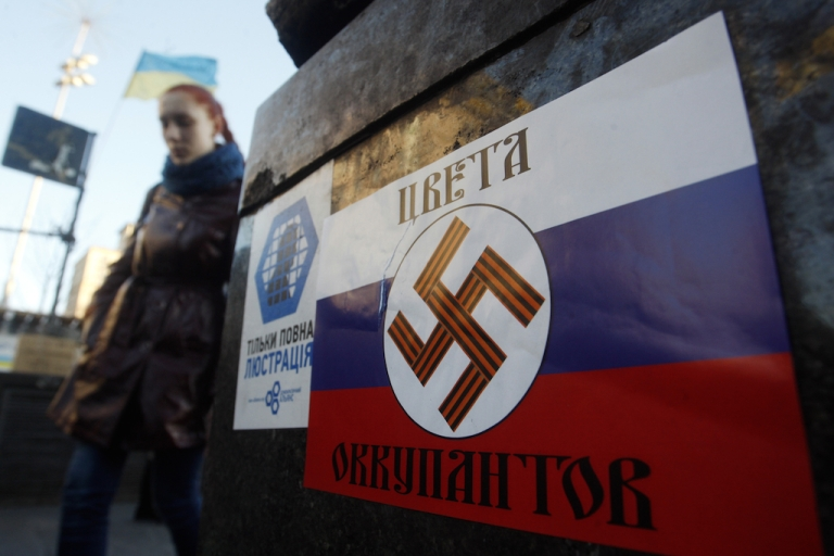 <p>Both sides are guilty of spin. This photo taken in Independence Square in the Ukraine capital of Kyiv on March 12, 2014, shows a poster with a Nazi swastika overlaid on a Russian flag that says