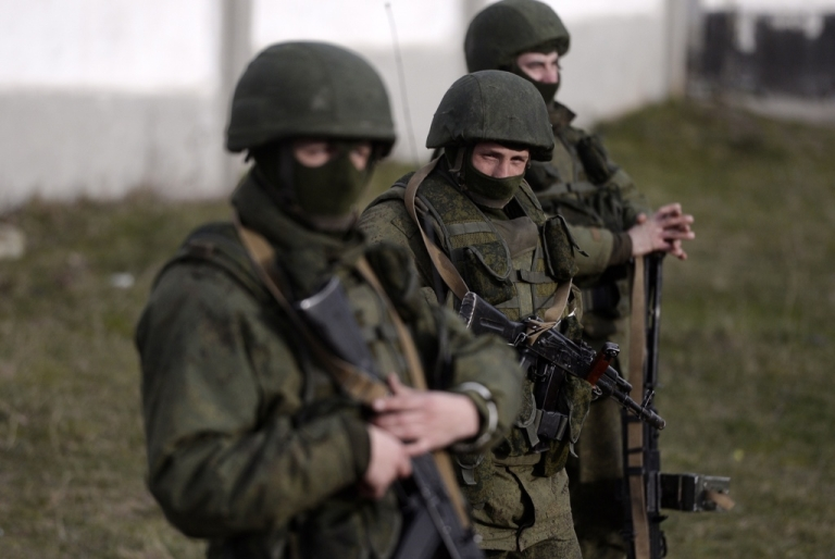 <p>Armed men, believed to be Russian servicemen, stand guard outside a Ukrainian military base in Crimea on March 16, 2014.</p>