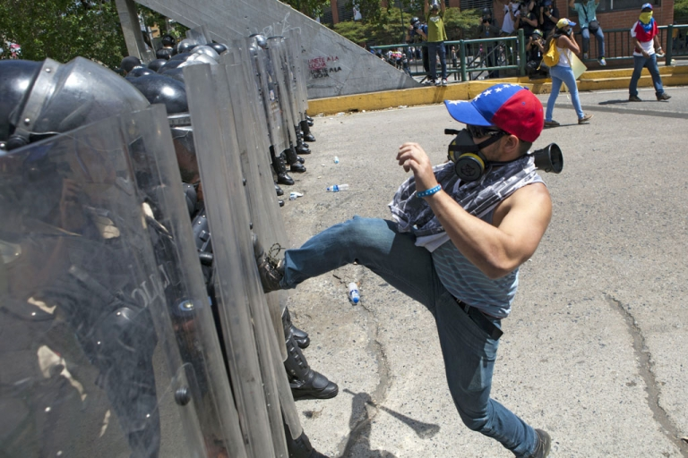 <p>A demonstrator confronts the National Police during a protest against Venezuelan President Nicolas Maduro, in Caracas, on March 20, 2014</p>