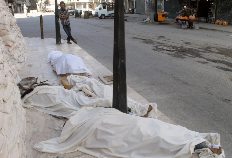 <p>A man stands looking at bodies wrapped in shrouds lying on the ground following a reported air strike by government forces on May 30, 2014 in Aleppo.</p>