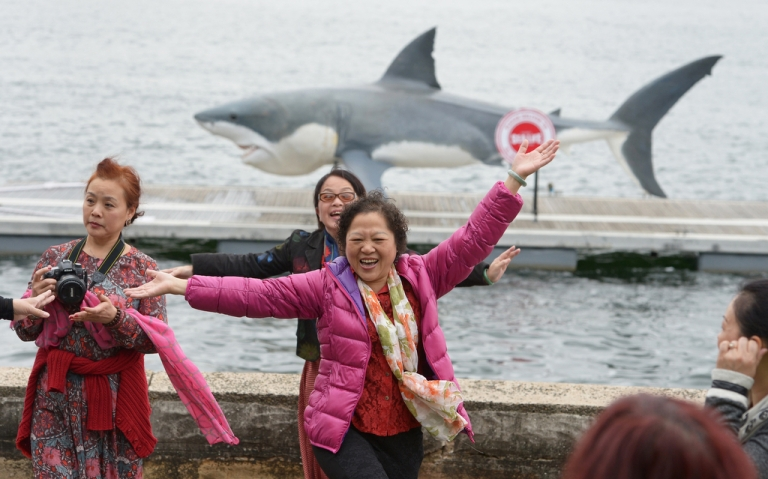 <p>Chinese tourists pose for a photo in front of 24-foot great white shark replica in Sydney on Nov. 26, 2013.</p>