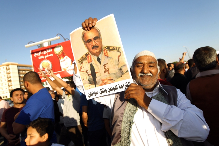<p>A Libyan carries a portrait of retired Gen. Khalifa Haftar during a rally in support of the rogue former general whose forces have launched a