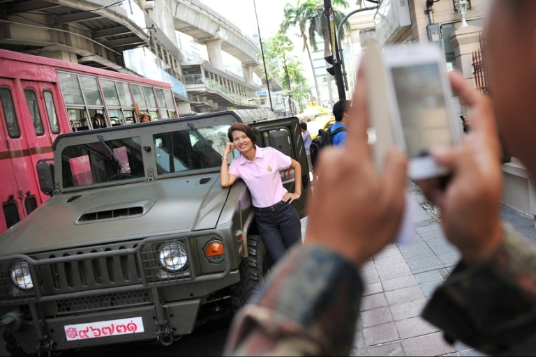 <p>A woman poses for a photo as Thai army soldiers deploy on a downtown street after martial law was declared on May 20, 2014 in Bangkok.</p>