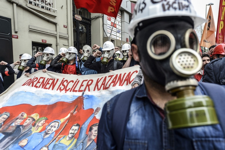 <p>Turkish protesters wearing gas masks hold a banner reading 'Workers who resist win' as they march towards Taksim Square in Istanbul during a May Day rally on May 1, 2014.</p>