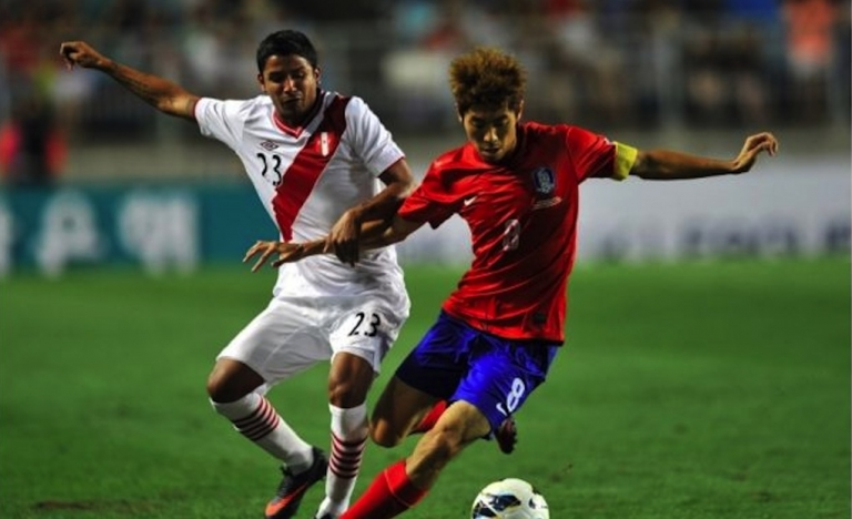 <p>Peru's Reimond Manco, left, vies for the ball with South Korea's Ha Dae-Sung during a friendly soccer game on Aug. 14, 2013.</p>