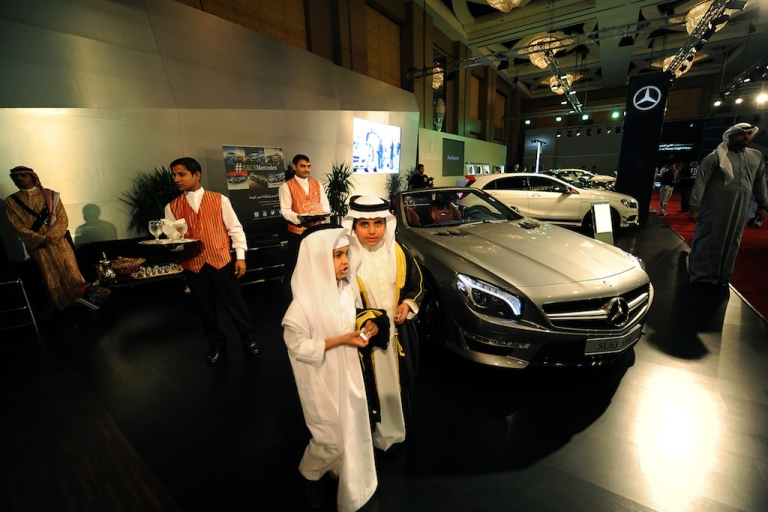 <p>Saudi boys walk past luxury Mercedes cars displayed at the 2013 International Luxury Motor Show in the capital Riyadh on October 29, 2013.</p>