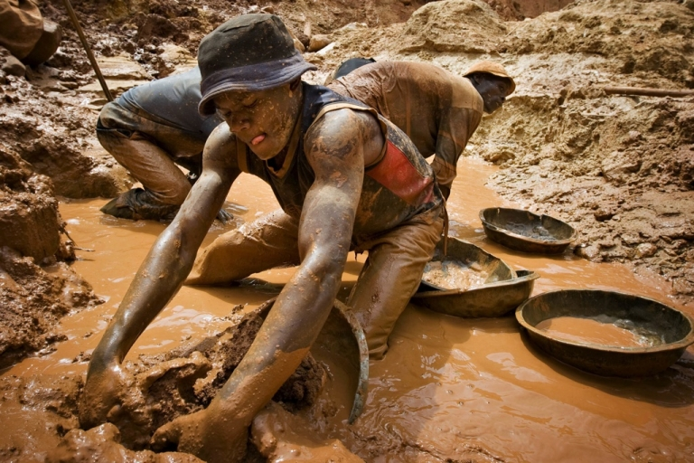 <p>A miner scoops mud while digging an open pit at the Chudja mine in the Kilomoto concession near the village of Kobu, 62 miles from Bunia in northeastern Congo, Feb. 23, 2009. Civil conflict in Congo has been driven for more than a decade by the violent struggle for control over the country's vast natural resources, including gold, coltan, diamonds and timber, most of which is exploited using hard manual labour.</p>