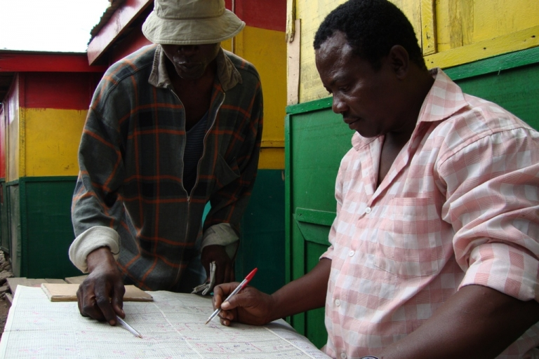 <p>Ghanaian lottery forecaster William Galley, right, consults extensive charts to make a prediction about what will be the lucky numbers in the next day's lotto. Many who bet on the national lottery seek the advice of forecasters like Galley, and if they win they return to pay them