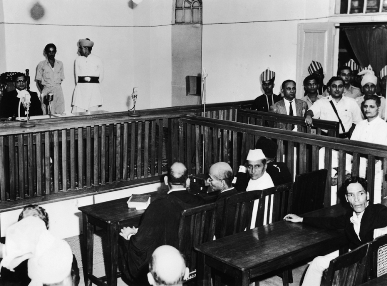 <p>Nathuram Vinayak Godse, bottom right, on trial for the assassination of Mahatma Gandhi in the red fort, Old Delhi, May 27, 1948. The presiding judge Atma Charan is on the left.</p>