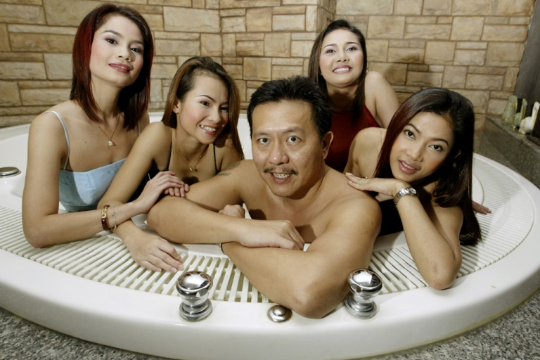<p>Thailand's massage parlor tycoon Chuwit Kamolvisit (center) poses in a jacuzzi inside Copa Cabana, one of the six upscale entertainment clubs he owned in Bangkok on Aug. 2, 2003.</p>