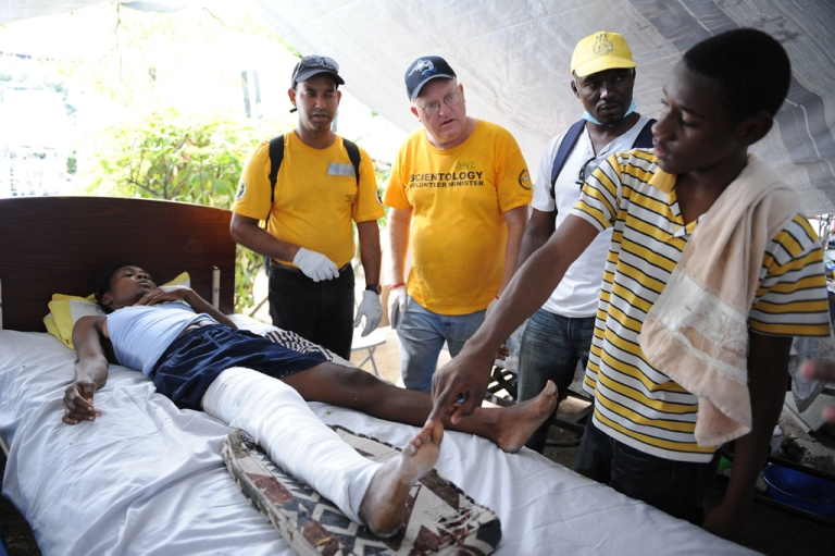 <p>Scientologists Dave McGregor (second from the left) and Ricardo Garcia (left) teach a relative of a patient their touch healing treatment method at a hospital in Port-au-Prince on Jan. 26, 2010.</p>