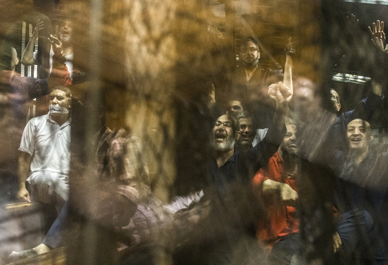 The Muslim Brotherhood's Safwat Hegazy (C) shouts from behind the defendants' cage as a judge reads out the verdict sentencing him and more than 100 other defendants to death on May 16, 2015 at the police academy in Cairo.
