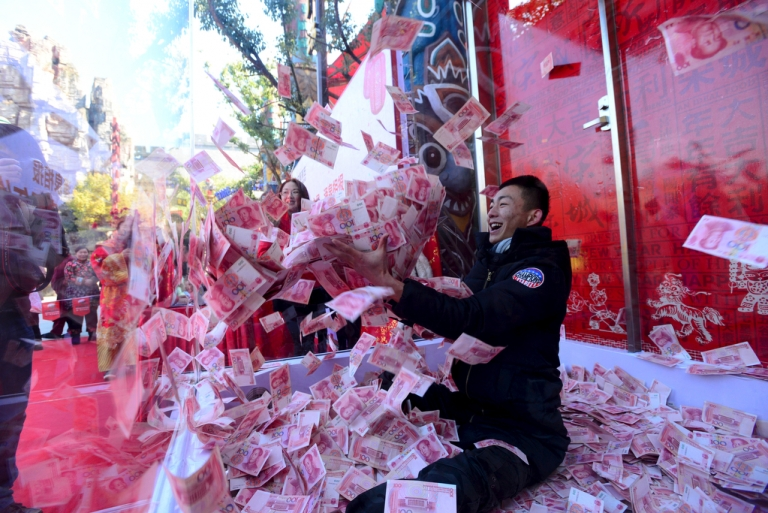 A man tries to snatch 100-yuan banknotes inside a glass cage during an event held to celebrate the upcoming Spring Festival, at a park in Hangzhou, Zhejiang province, China, on Jan. 26, 2016.
