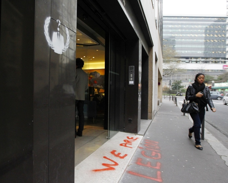 <p>A woman walks past a graffiti made by the shadowy online hackers group Anonymous at the entrance of the French anti-piracy watchdog Hadopi headquarters on January 30, 2012 in Paris.</p>