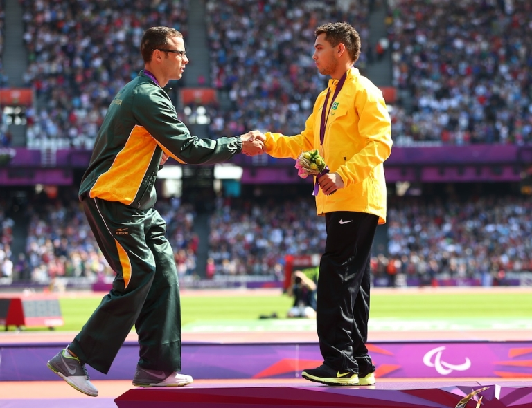 <p>Silver medalist Oscar Pistorius of South Africa shakes hands with the gold medalist Alan Fonteles Cardoso Oliveira on the podium during the medal ceremony for the Men's 200m - T44 on day 5 of the London 2012 Paralympic Games at Olympic Stadium on September 3, 2012 in London, England.</p>