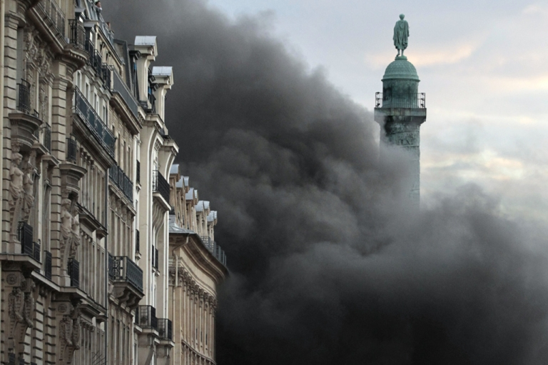 <p>A cloud of black smoke envelops the Place Vendôme column, on March 8, 2012 in Paris, after a fire - which appears to have started in the nearby Hotel Ritz underground parking lot - broke out.</p>