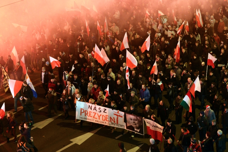 <p>Nationalist protesters hold Polish flags and carry a banner with the picture of former President Lech Kaczynski as they march the street of Warsaw during Independence Day celebrations on November 11, 2012.</p>