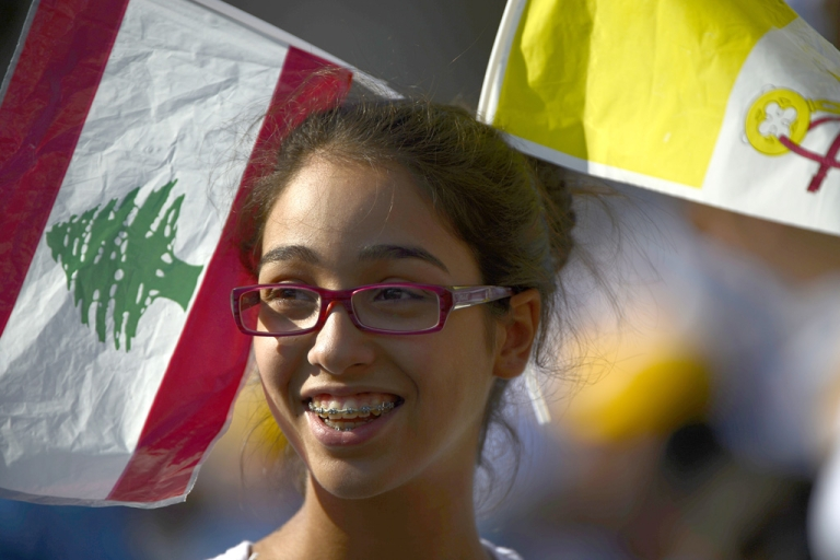 <p>A girl smiles as she waits in the Lebanese mountain village of Bkerke, overlooking the capital Beirut,  for the arrival of Pope Benedict XVI on September 15, 2012.  Pope Benedict XVI urged Middle Eastern Christians and Muslims to forge a harmonious, pluralistic society in which the dignity of each person is respected and the right to worship in peace is guaranteed.</p>