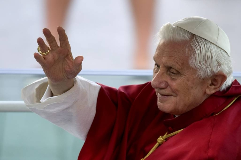 <p>Pope Benedict XVI waves to faithful as he leaves the Almudena Cathedral in his popemobile after celebrating a mass during the World Youth Day festivities in Madrid.</p>