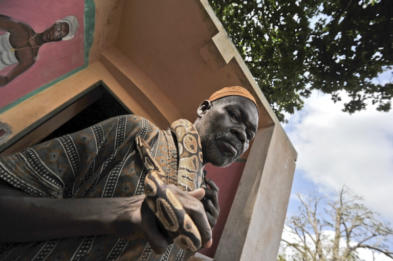 <p>Agbotabatoh Dah Deh, a Benin resident caretaker of the Temple of Pythons, a centre of voodoo, holds a python around his neck in front of the temple, on November 16, 2011 in Ouidah, 25 miles from Cotonou. Pope Benedict XVI makes his second visit to Africa as pontiff when he arrives in Benin on November 18, 2011, and he will meet a situation where Catholic and traditional beliefs exist side-by-side and often mix.</p>