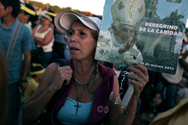 <p>A woman waits for the arrival of Pope Benedict XVI for his mass at Havana's Revolution Square on the last day of his three day visit on March 28, 2012 in Havana, Cuba. Fourteen years after Pope John Paul II visited Cuba, Pope Benedict is making his first trip to the communist country.</p>