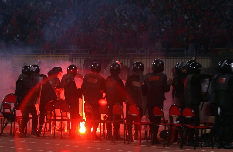 <p>Egyptian riot policemen stand guard as a flare is thrown during a football match between al-Masry and al-Ahly in Port Said on February 1, 2012.</p>