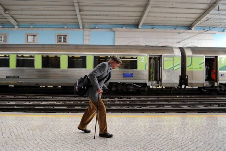 <p>An elderly man walks to his train at the Santa Apolonia train station in Lisbon, on March 28, 2011.</p>