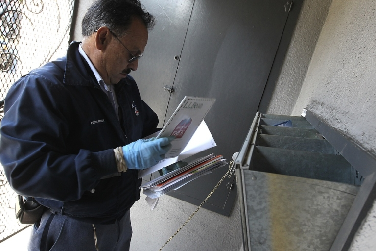 <p>US Postal Service letter carrier Juan Padilla puts letters into a mailbox as he walks his delivery route on Dec. 5, 2011, in San Francisco, Calif.</p>