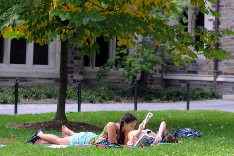 <p>Claudia Kelley (L), of San Francisco, California and Cameron Langford of Davidson, North Carolina lay on the grass and read in a courtyard at Princeton University in Princeton, New Jersey.</p>