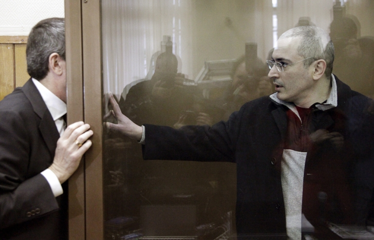 <p>Jailed Russian oil tycoon Mikhail Khodorkovsky talks to his lawyer through the bullet-proof glass defendents' cage at a Moscow court on March 31, 2009. The European Court of Human Rights ruled on Thursday that Khodorkovsky was not treated fairly during his trial but that the charges were sound.</p>